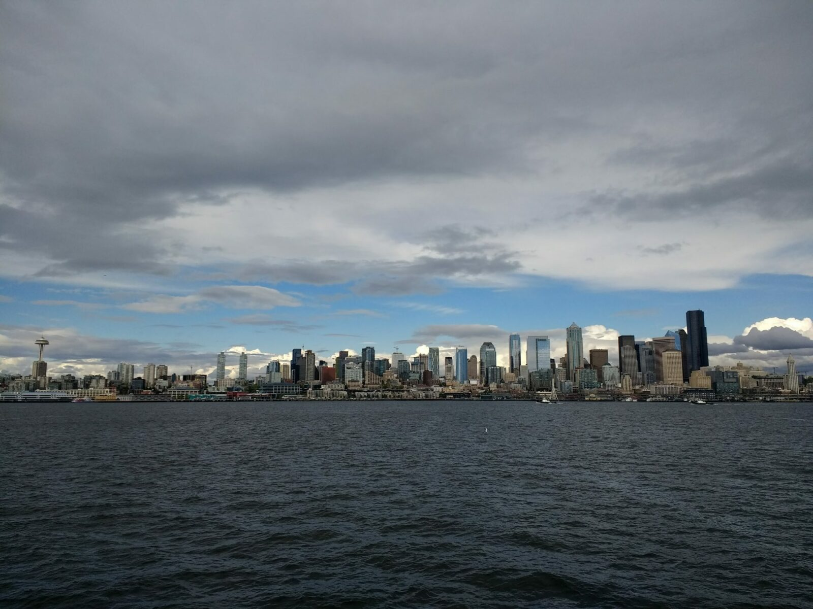 water and a city skyline against a cloudy sky