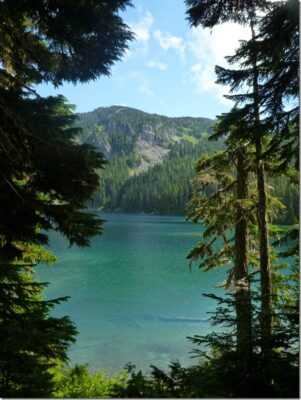 Mowich Lake in Mt Rainier National Park is the trailhead for the Spray Park trail. It is a turquoise blue color, surrounded by forested hillsides.