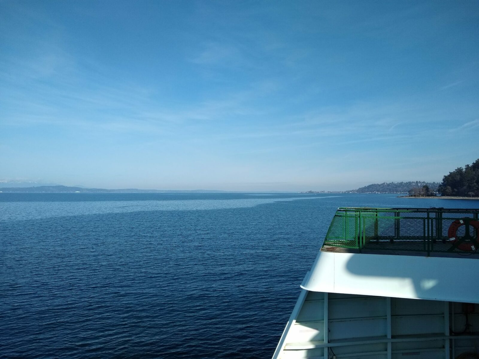 part of a ferry boat and the shoreline on a sunny day
