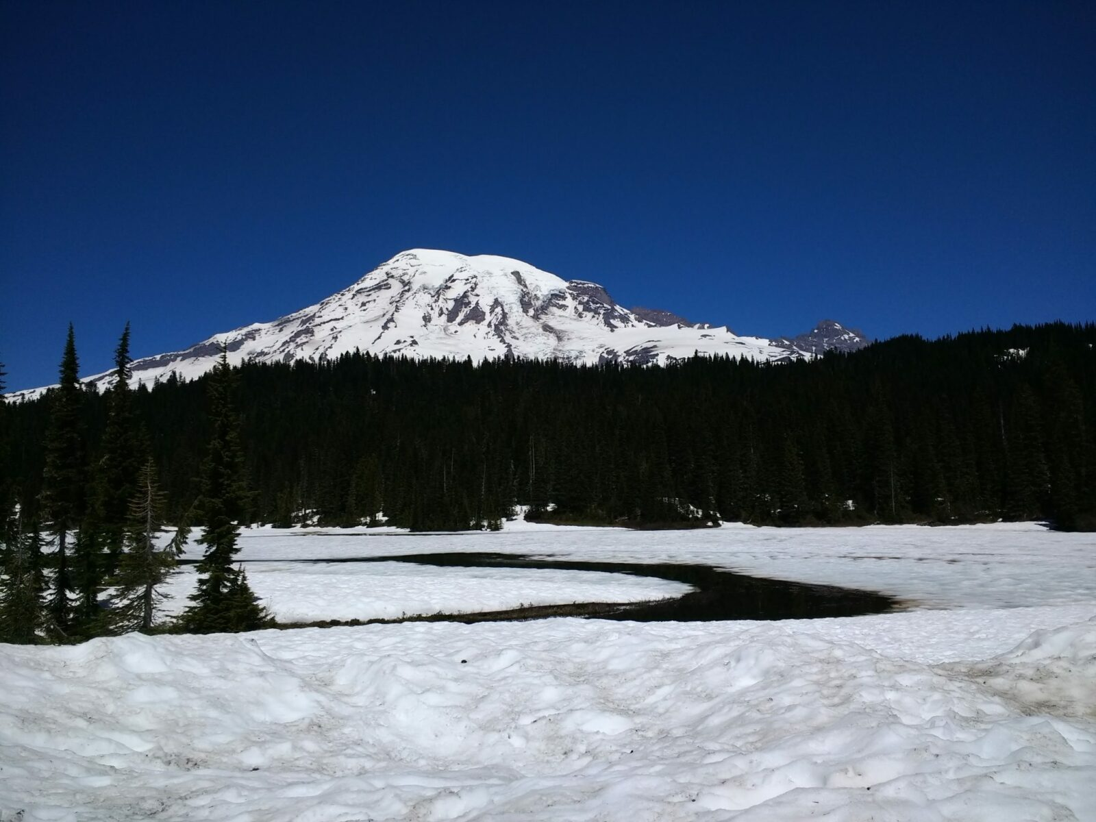 A large snow covered mountain behind forested hills. A partially frozen lake in the foreground