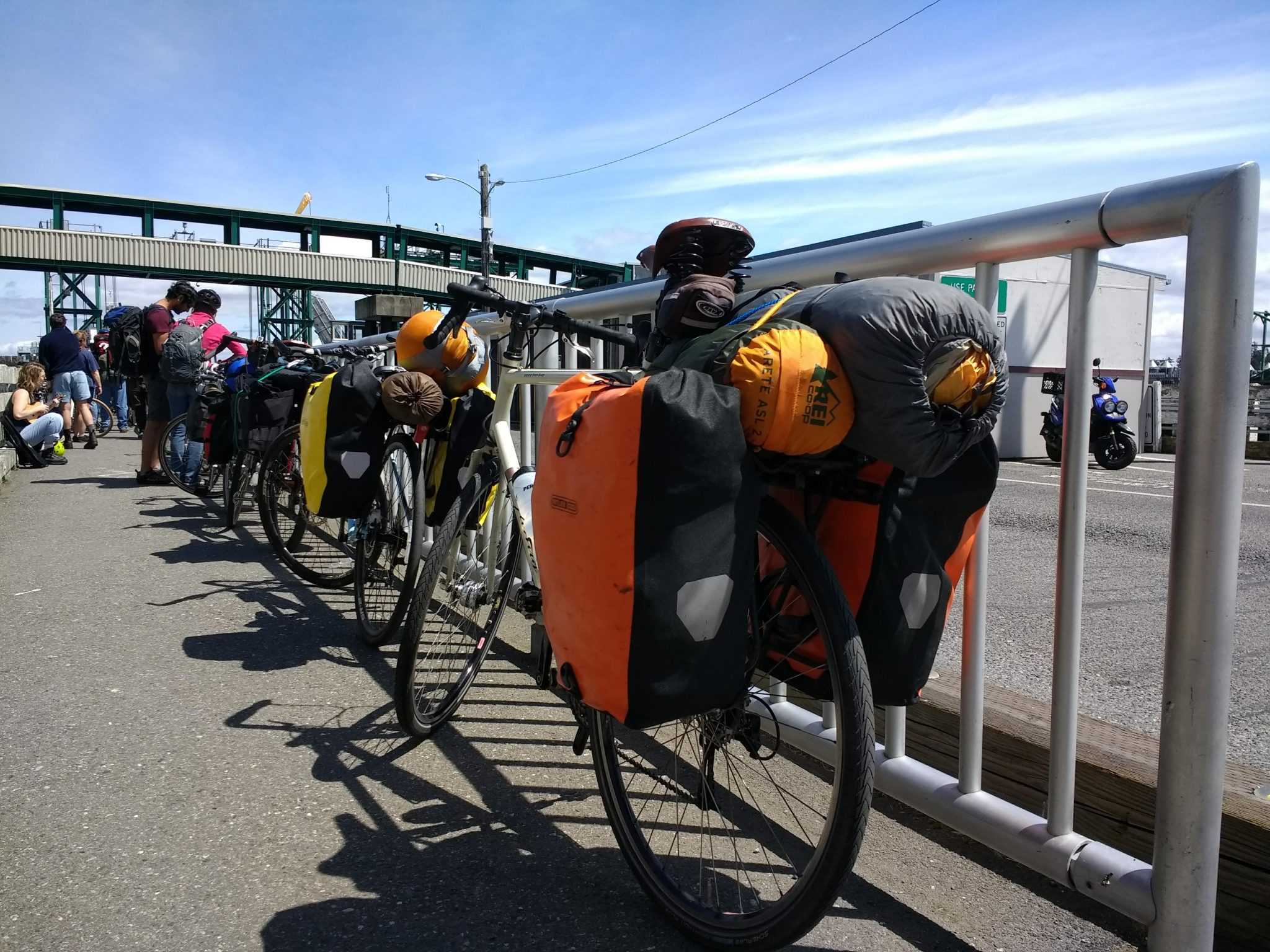 A group of bikes loaded with colorful camping gear next to a metal barrier on a dock, getting ready for Lopez Island bike camping