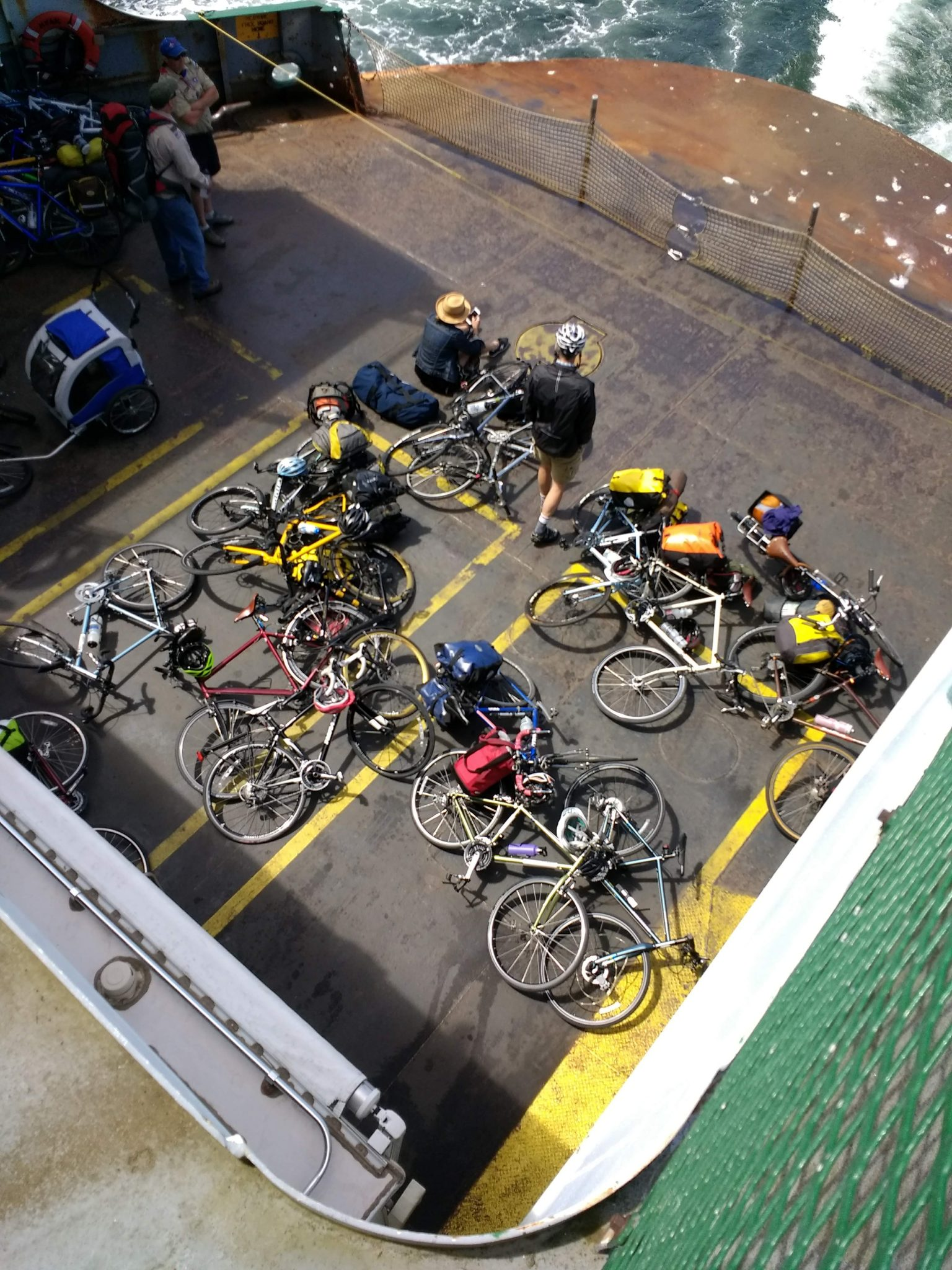 A pile of bikes laying down on the deck of the ferry from above coming back from Lopez Island bike camping. A few people are sitting around the bikes.