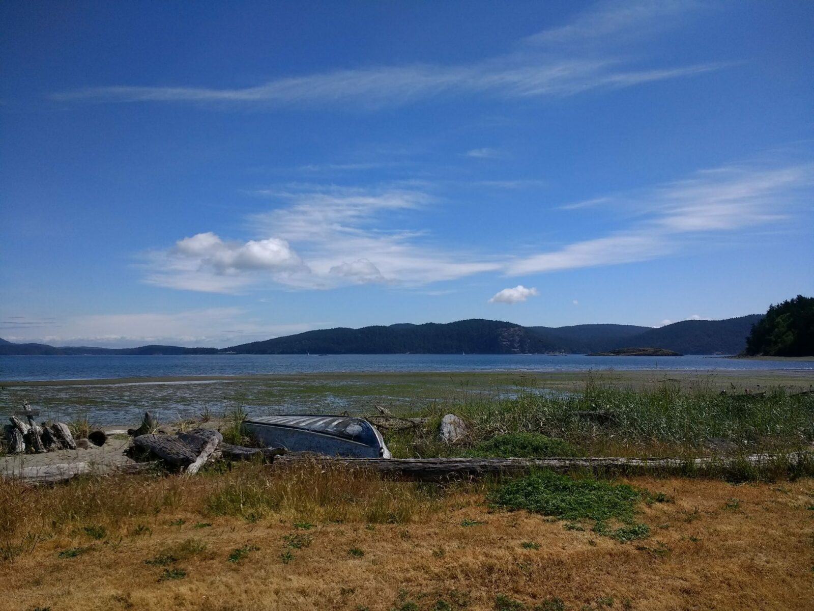 Camping in the San Juan Islands at Spencer Spit State Park. There is a grassy spit in the foreground wtih a canoe, tideflats and water behind. Forested islands are in the background on a sunny day
