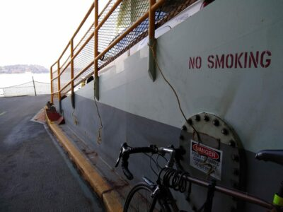 A bike tied with a rope to a metal railing on the Washington state ferry