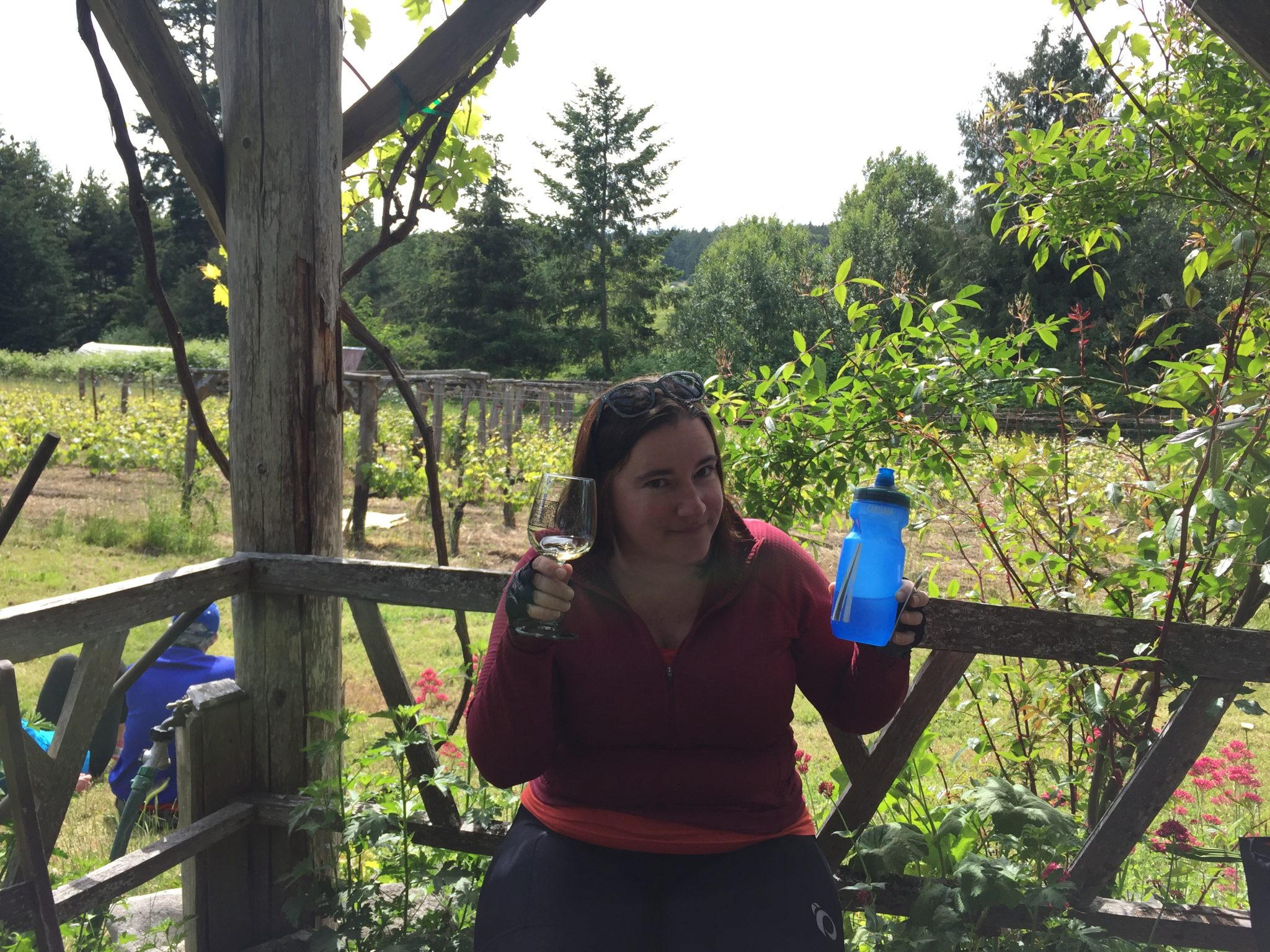 A woman is smiling on a patio in a vineyard. She is holding a wine glass and a biking waterbottle