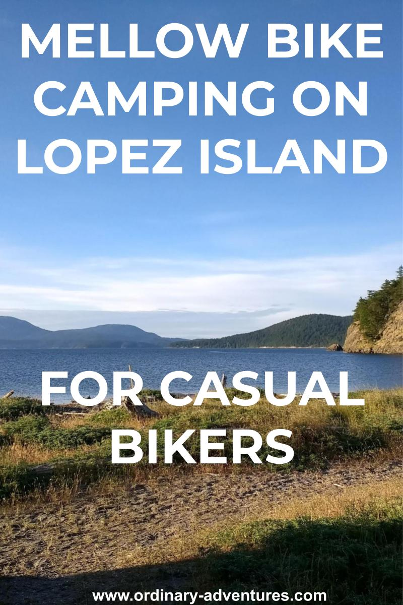 Lopez Island bike camping at Spencer Spit State Park. There is a grassy spit in the foreground wtih a canoe, tideflats and water behind. Forested islands are in the background on a sunny day. Text reads: Mellow bike camping on lopez island for casual bikers