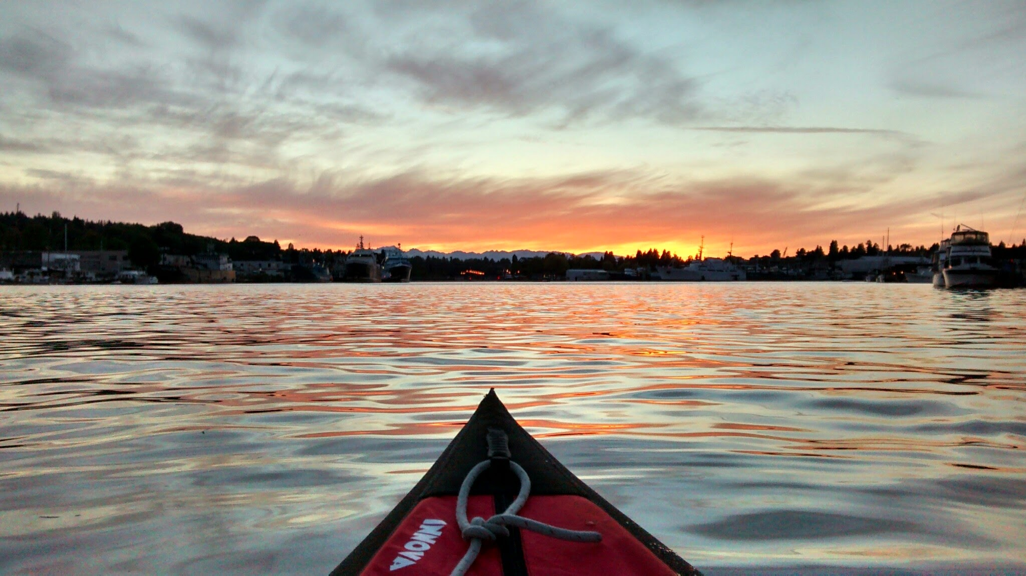 Rent kayaks in Seattle on the inland waterways of Seattle. A kayak bow is in the lake washington ship canal near gasworks park at sunset