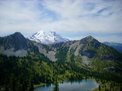 Mt Rainier behind a forested and rocky hillside which surrounds a blue, alpine lake. How to start hiking and enjoy these views!