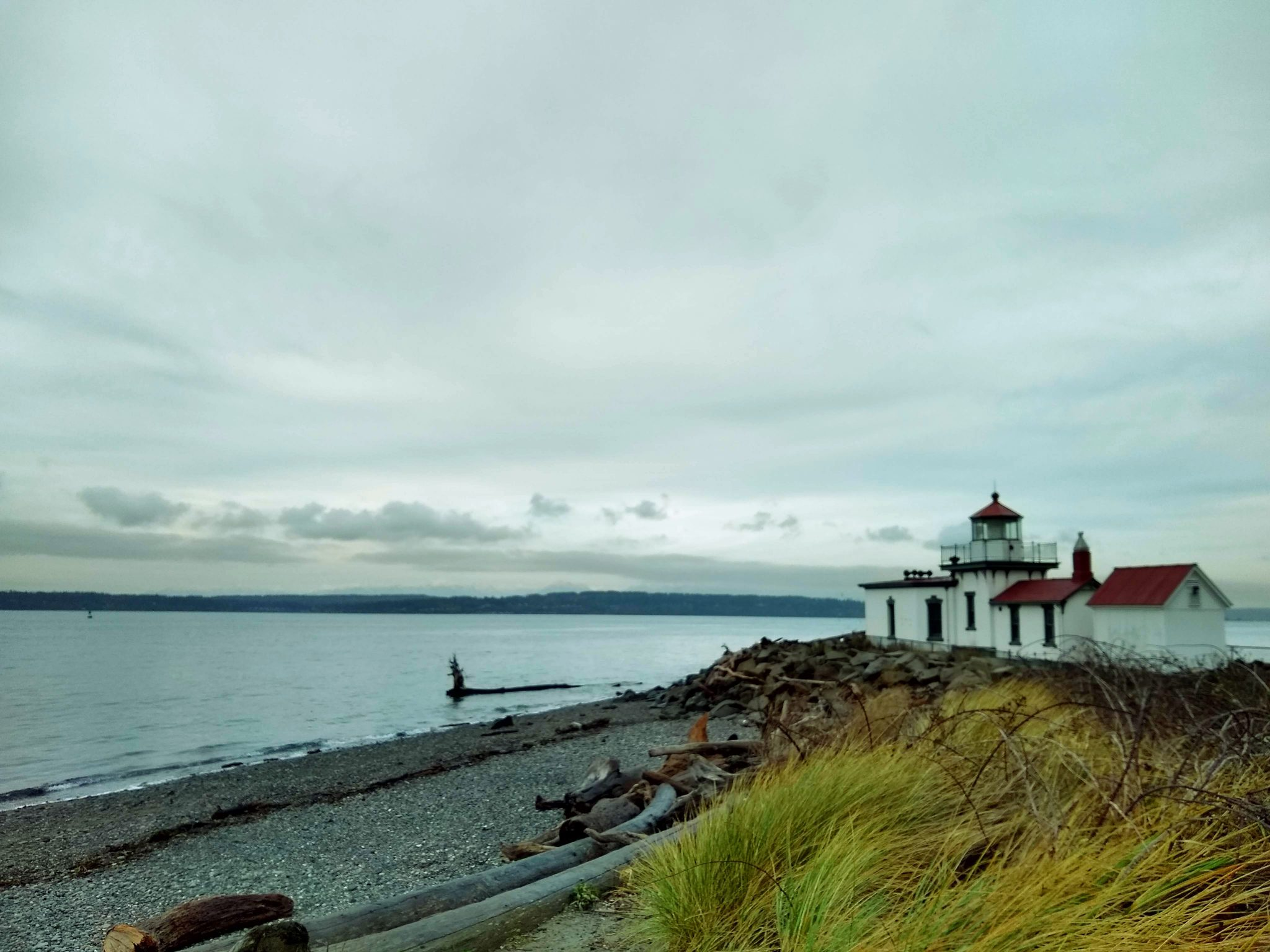Outdoor activities in Seattle include beaches such as this one by the Westpoint lighthouse. The lighthouse is on a gravel beach with driftwood and rocks. The water is calm and forested hills are seen across the water. It's an overcast day