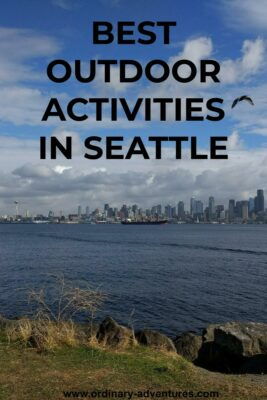 The Seattle skyline is seen from a distance across the water. There is a tanker ship in the harbor as well as a sailboat. There are two birds flying against a blue and cloudy sky. In the foreground on the shore there are rocks and grass. Text reads: Best Outdoor activities in Seatttle