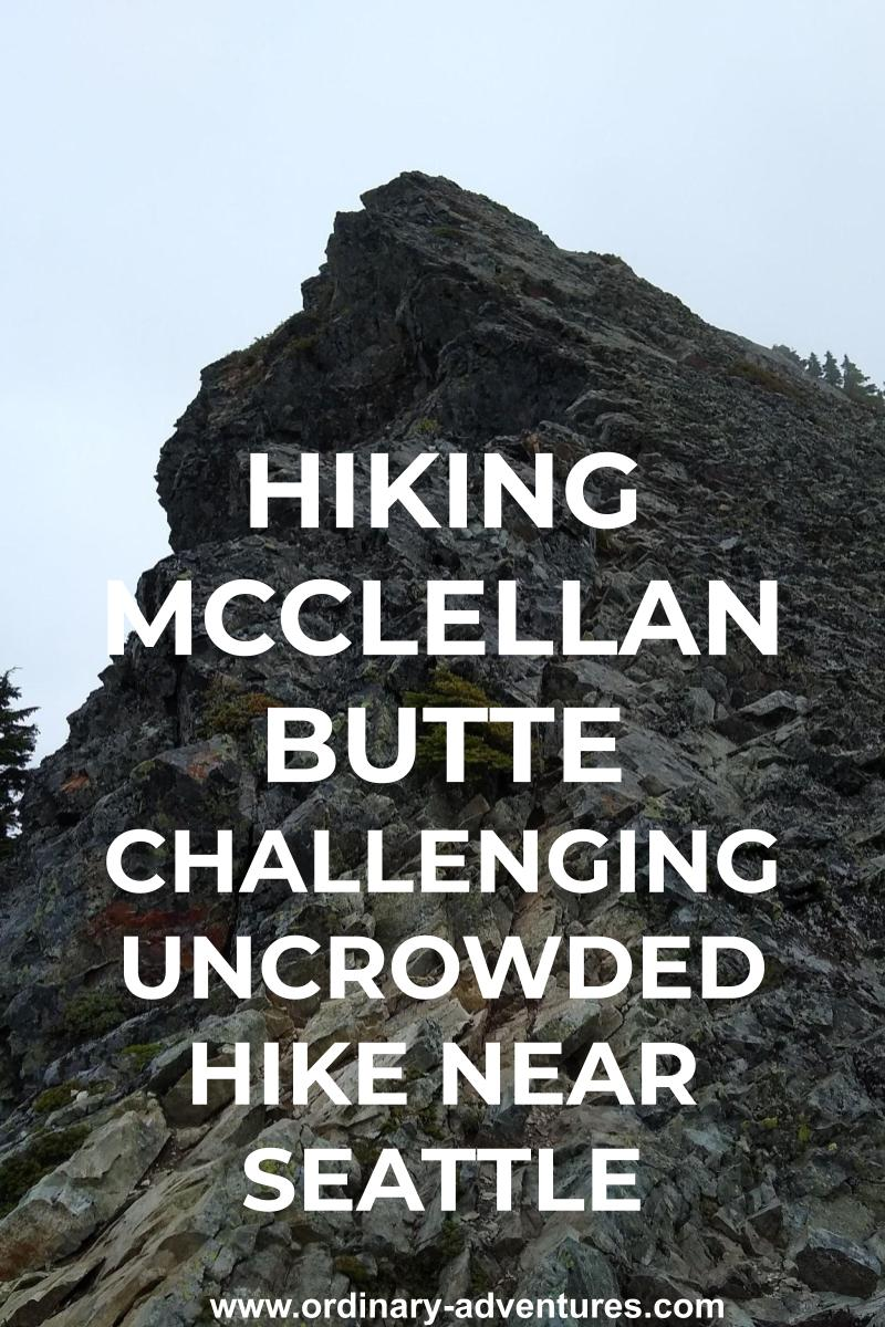 The summit block on the McClellan Butte hike. It is an angled gray rock sticking into the fog, surrounded with a few evergreen trees. Text reads: hiking McClellan Butte challenging uncrowded hike near seattle