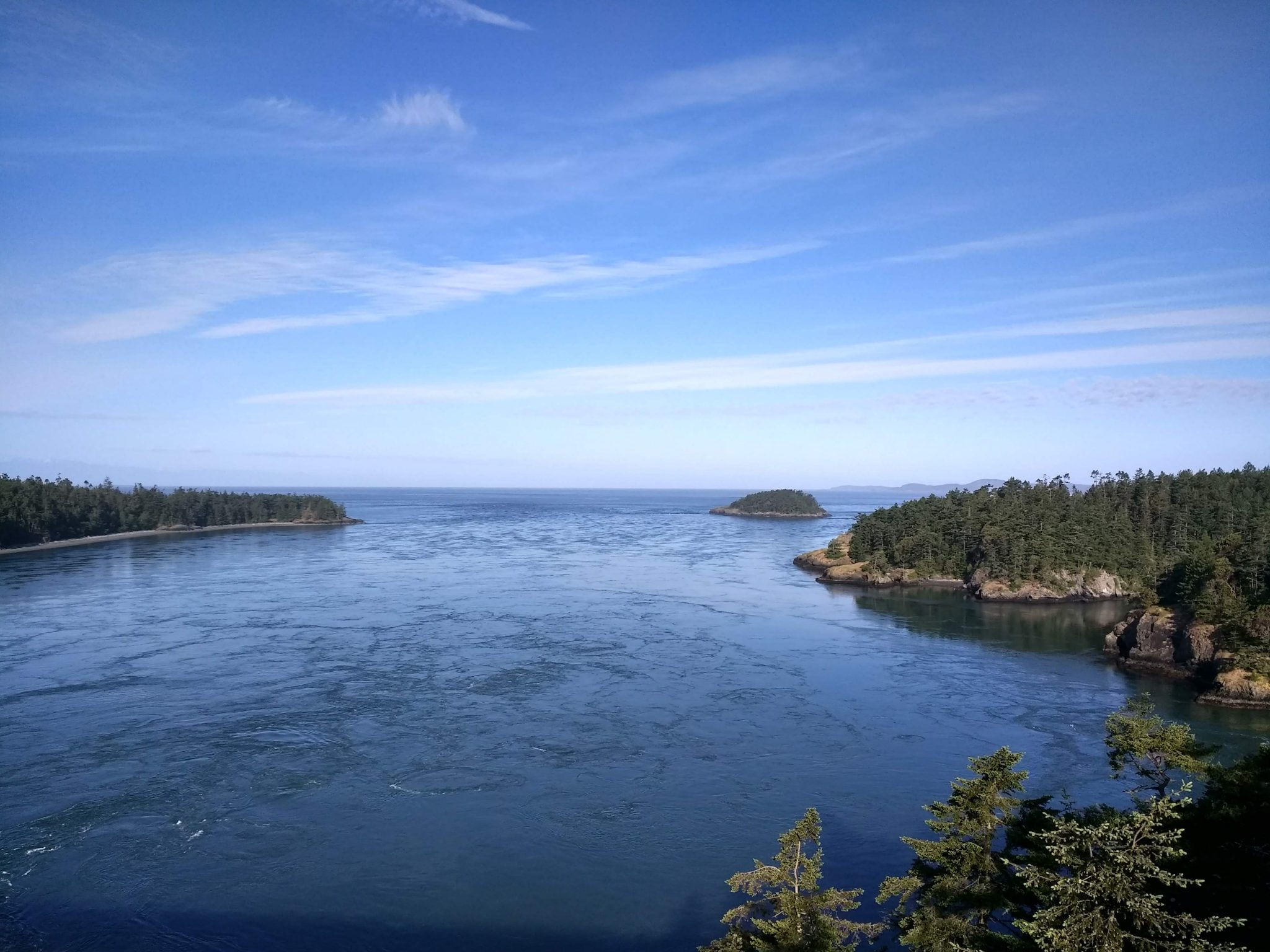 Several rocky island shores with forested hillsides are seen from above on a sunny day. The water has a current through Deception Pass and is bright blue. The sky is also blue with a few wispy clouds
