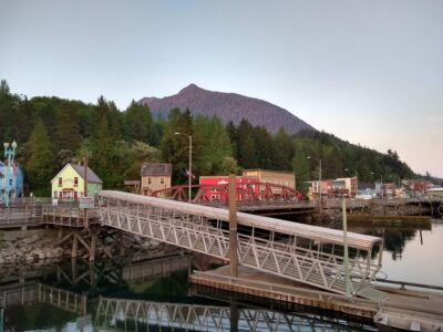 At the end of the day in Ketchikan Alaska, the harbor is quiet. There is a metal ramp going to a dock with colorful historic buildings in the background. There is an evergreen forest behind the houses and behind that the top of Deer Mountain rises above down