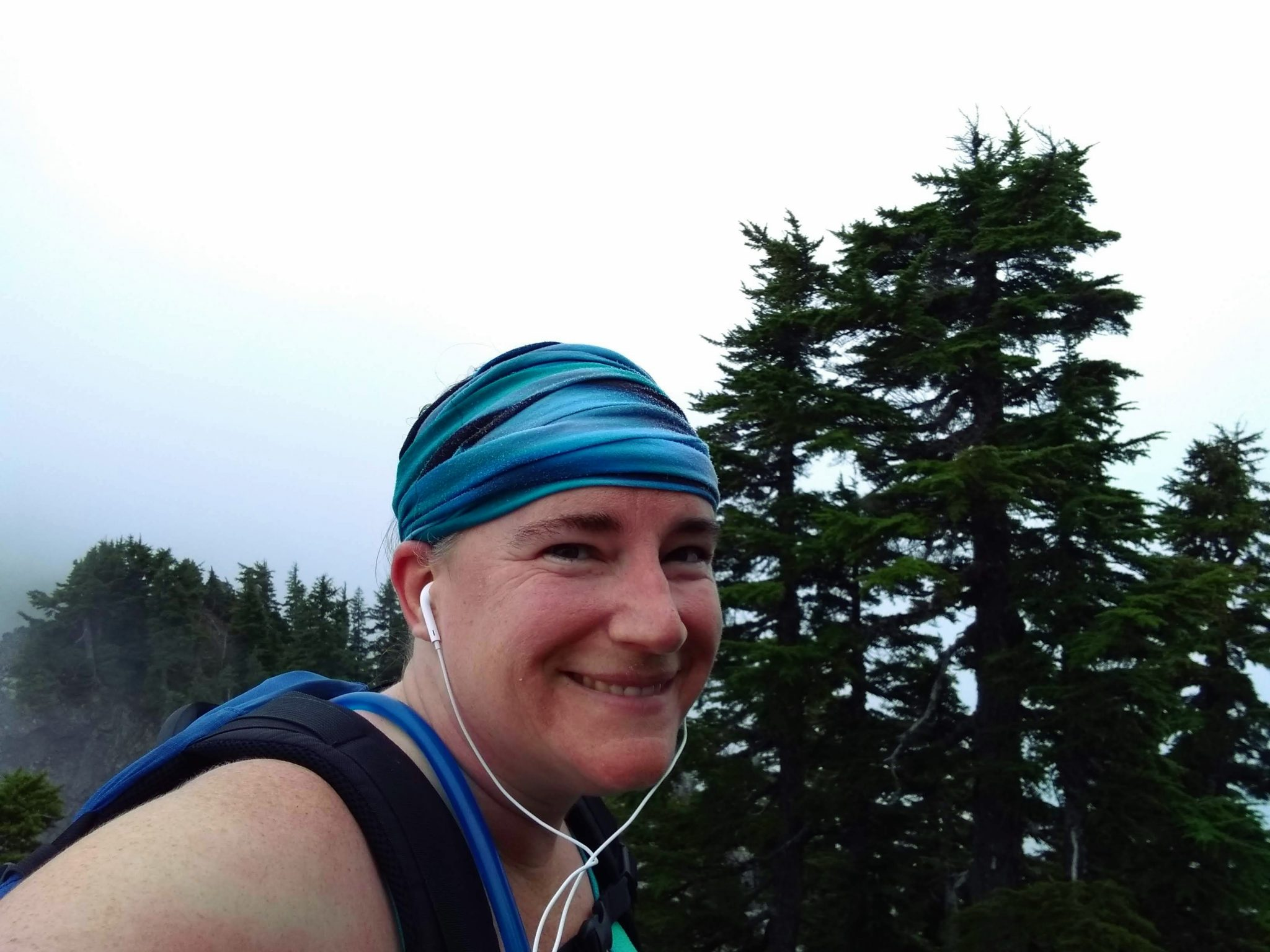 A smiling person on a mountain surrounded by trees in the fog. She is wearing white earbuds, a head wrap, tank top and a backpack.