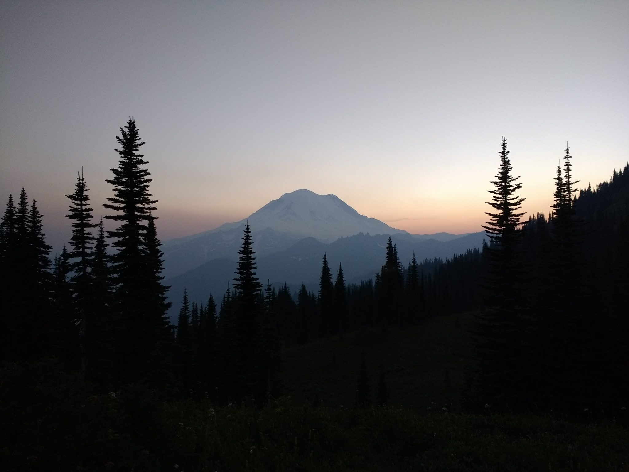 On the Naches Peak Loop hike, Mt Rainier views are amazing! Here it is sunset and getting dark. Evergreen trees are silouetted in the foreground. In the background, a fading sunset illuminates the summit of Mt Rainier