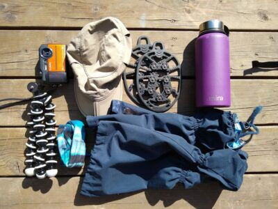 Extra things to pack for a hike day hiking gear on a wooden deck, including a camera, tripod, hat, gaiters, rubber ice grippers for shoes and a purple water bottle