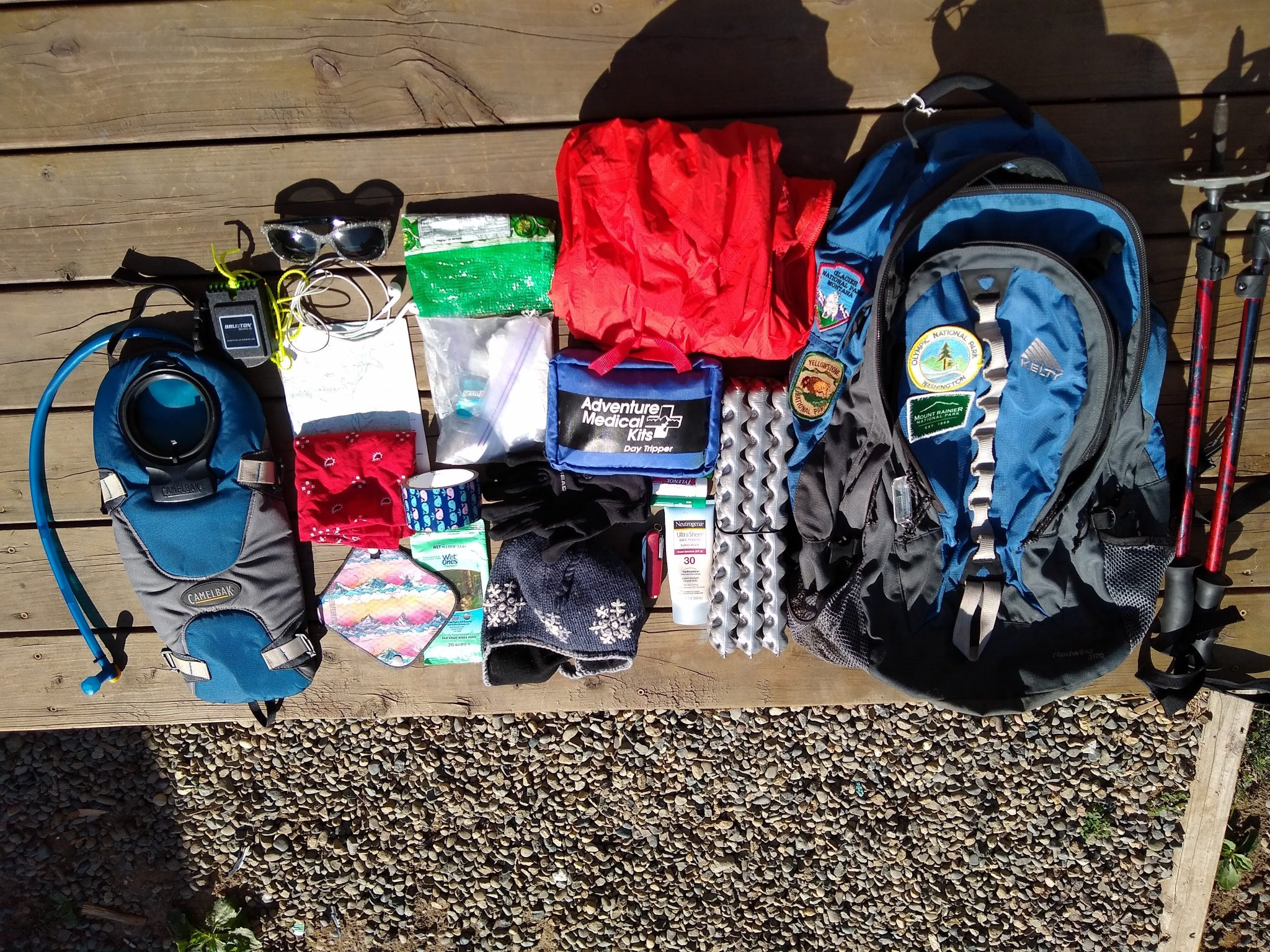 what I pack for a hike: A blue backpack and lots of day hiking gear, including trekking poles, a red rainjacket, a first aid kit, a sit pad, head net, water bladder, sunglases and a map