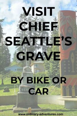 A tall gray gravestone is surrounded by a red and black painted pole in a grassy area. There are evergreen trees and houses in the background. Text reads: Visit Chief Seattle's grave by bike or car