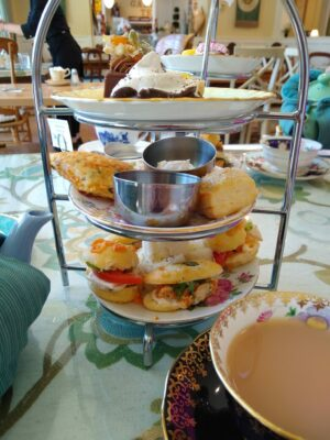 A tiered tray in a restaurant with a variety of sandwiches and pastries on a table. There is also a cup of tea in a china cup.