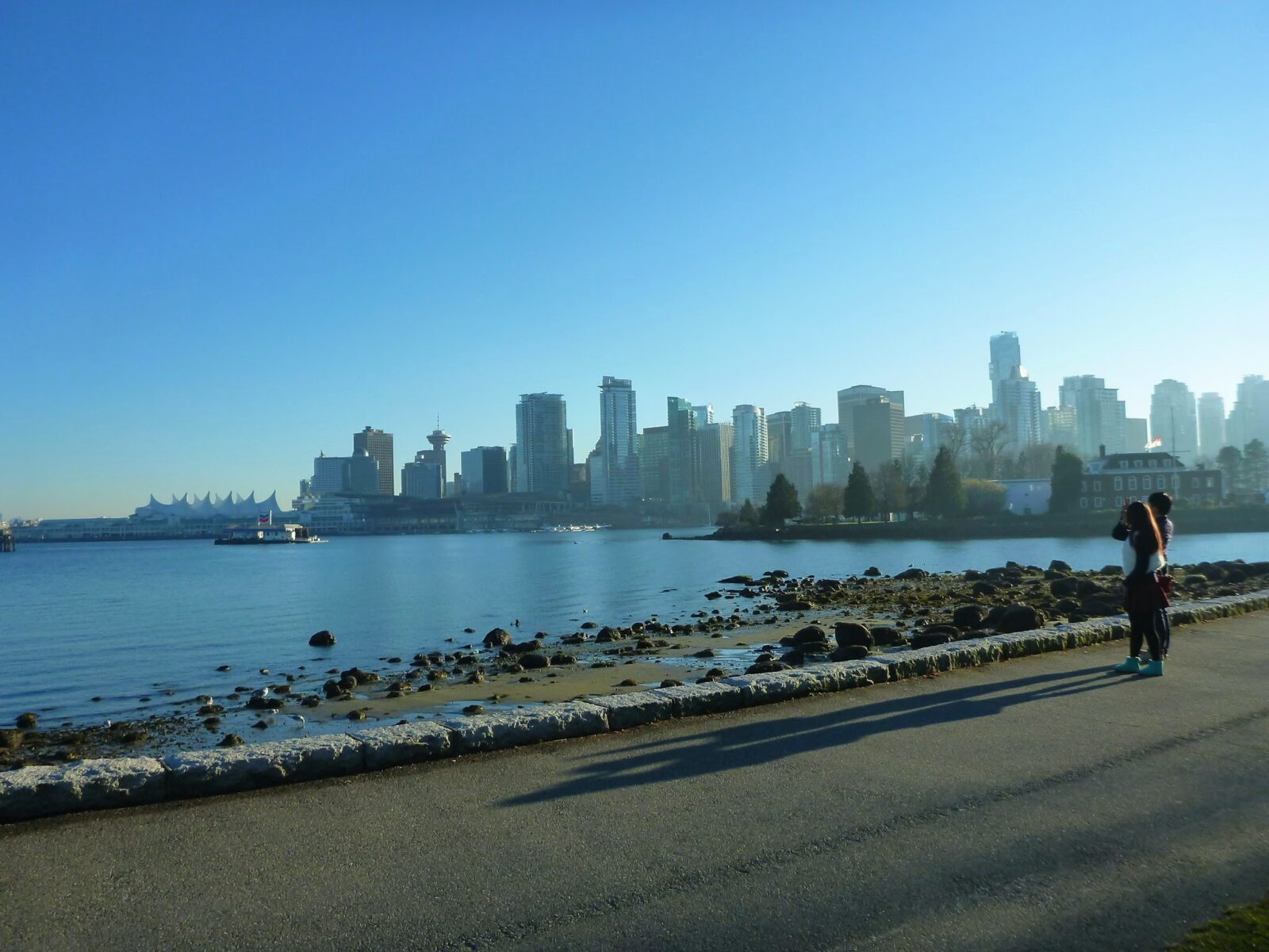 A city skyline is seen in the distance across a body of water. In the foreground is a paved trail and a rocky beach. It's a blue sky sunny day on the Stanley Park Seawall in Vancouver, Canada one of the best weekend getaways from seattle