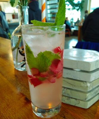 A fancy drink on a wooden bar in a clear glass. The drink is milky colored and has brightly colored mint and chopped rhubarb floating in it. One of the best things to do in Juneau!