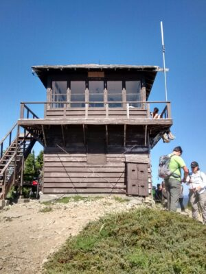 A brown painted fire lookout on a clear, sunny day. Hikers are standing around it, looking at the view as well as adjusting their gear. The lookout is sitting on top of a rocky summit with some green brush
