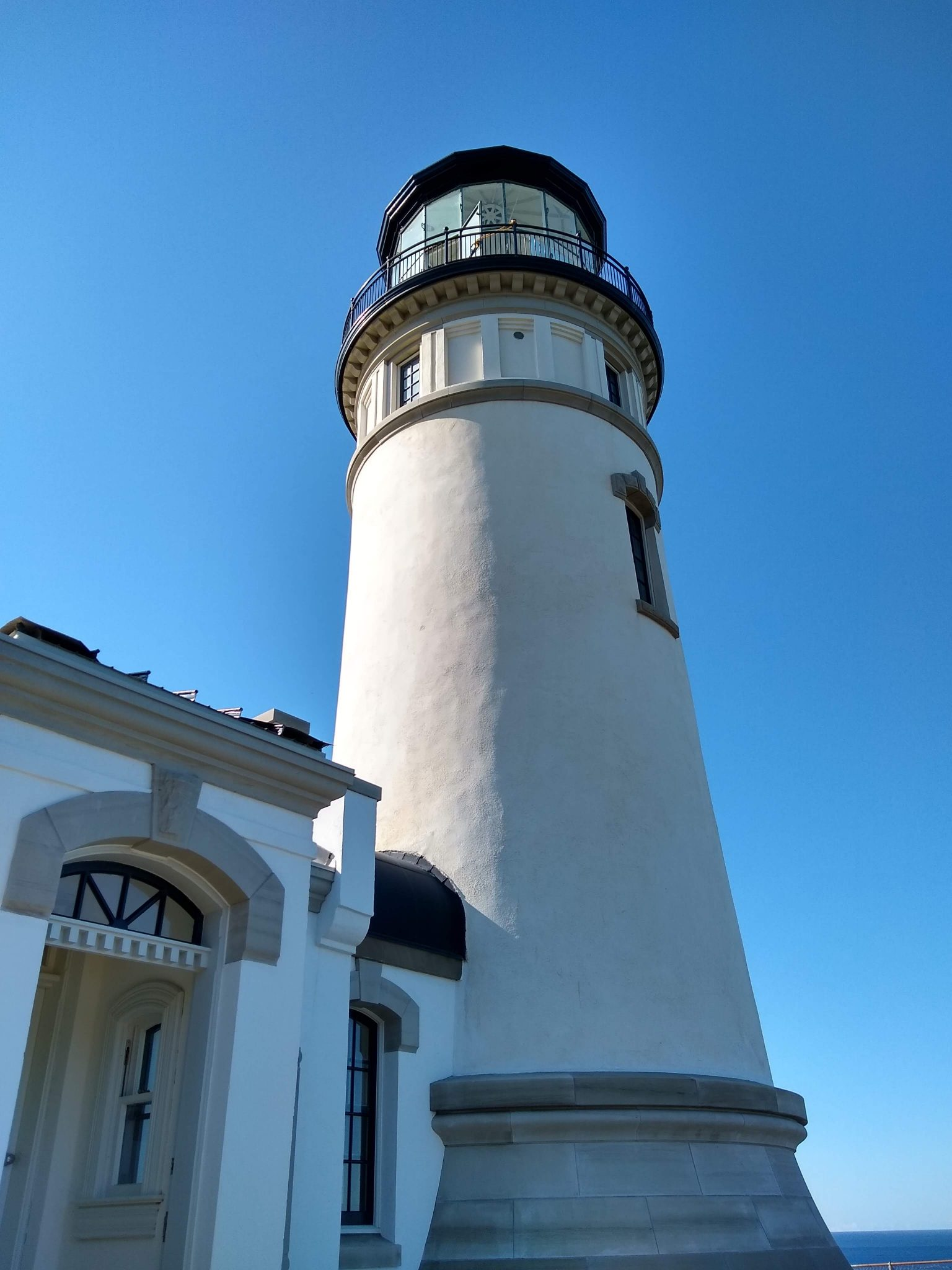 A close up of a bright white lighthouse built in 1898. There is blue sky behind it and a bit of the ocean is visible.