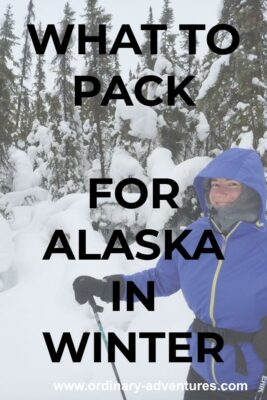 A person holding ski poles and dressed in lots of warm clothes on a snowy day in the forest. The person is smiling. Text reads: What to pack for Alaska in winter