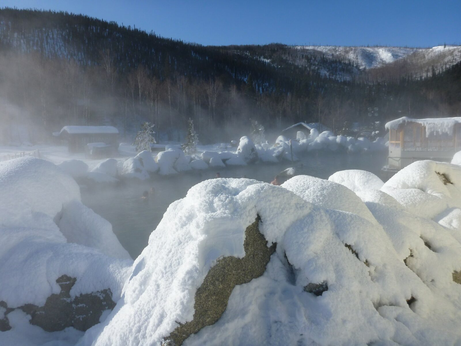 wintry hot springs surrounded by icy and snowy rocks at Chena Hot springs