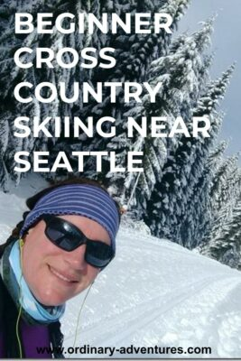 A woman wearing sunglasses smiles on a cross country ski trail. There are snow covered evergreen trees all around her. Text reads: Beginner cross country skiing near Seattle