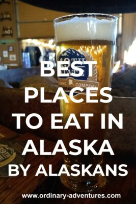 A beer in a pint glass on a wooden table in a restaurant in Alaska. Text reads: Best places to eat in Alaska by Alaskans