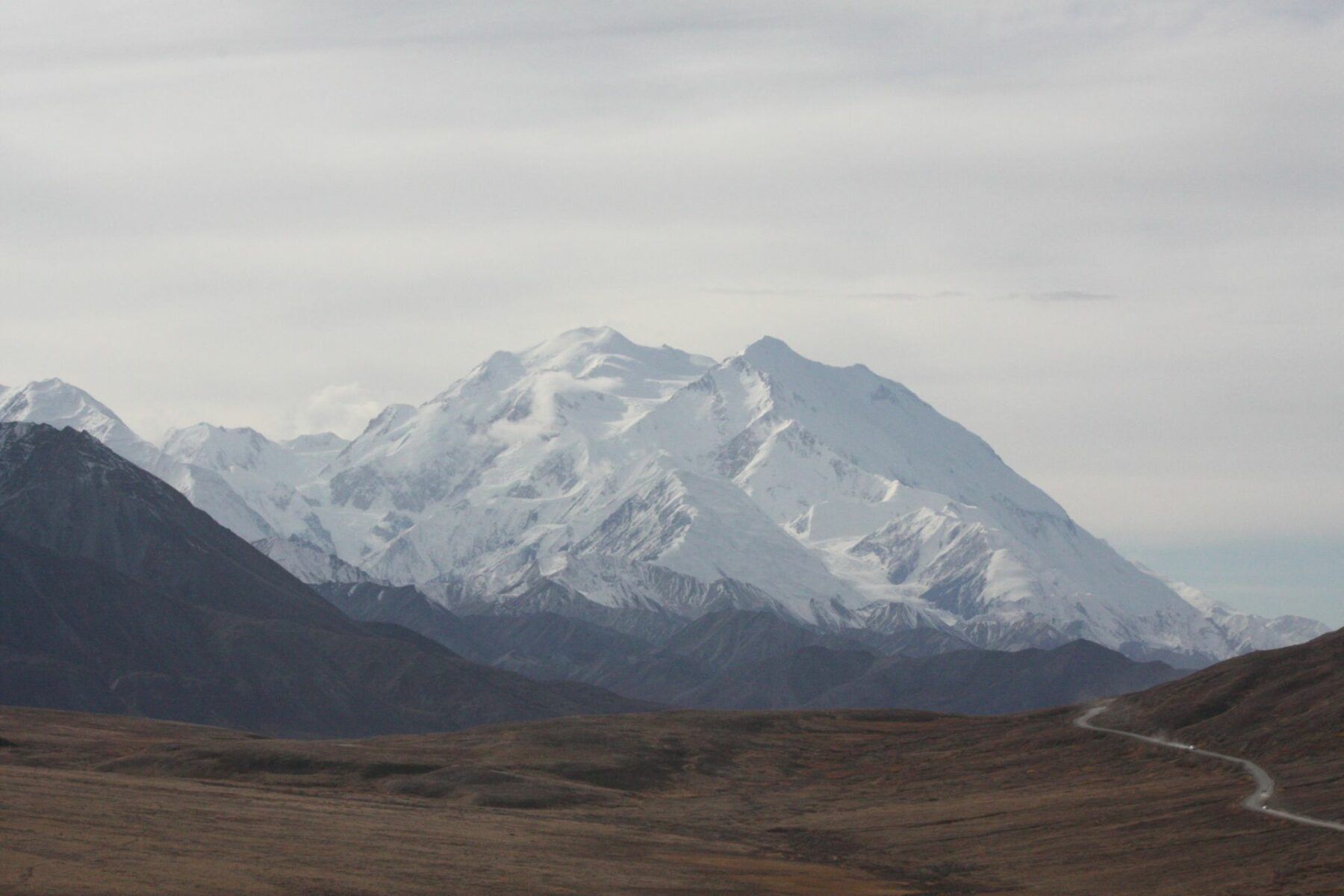 Denali, the High One, is seen across a valley in Denali National Park, a popular Alaska National park. There is a road following the valley.