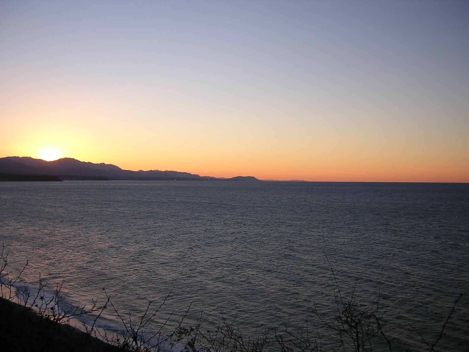 A winter sunset at the Dungeness Wildlife Refuge. The sun has just set behind the mountains and the water is dark gray. There are bushes in the foreground