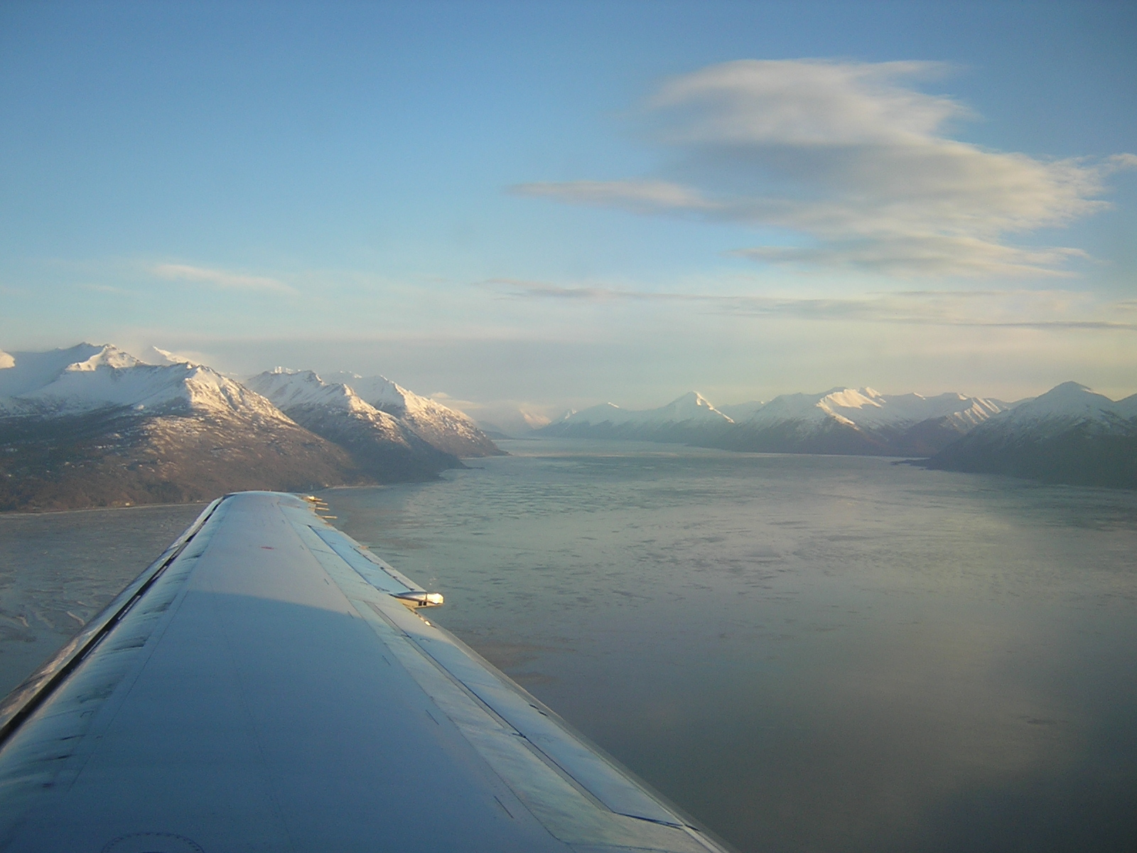 An airplane wing flying into Anchorage Alaska. Water and snow covered mountains are visible on a sunny day