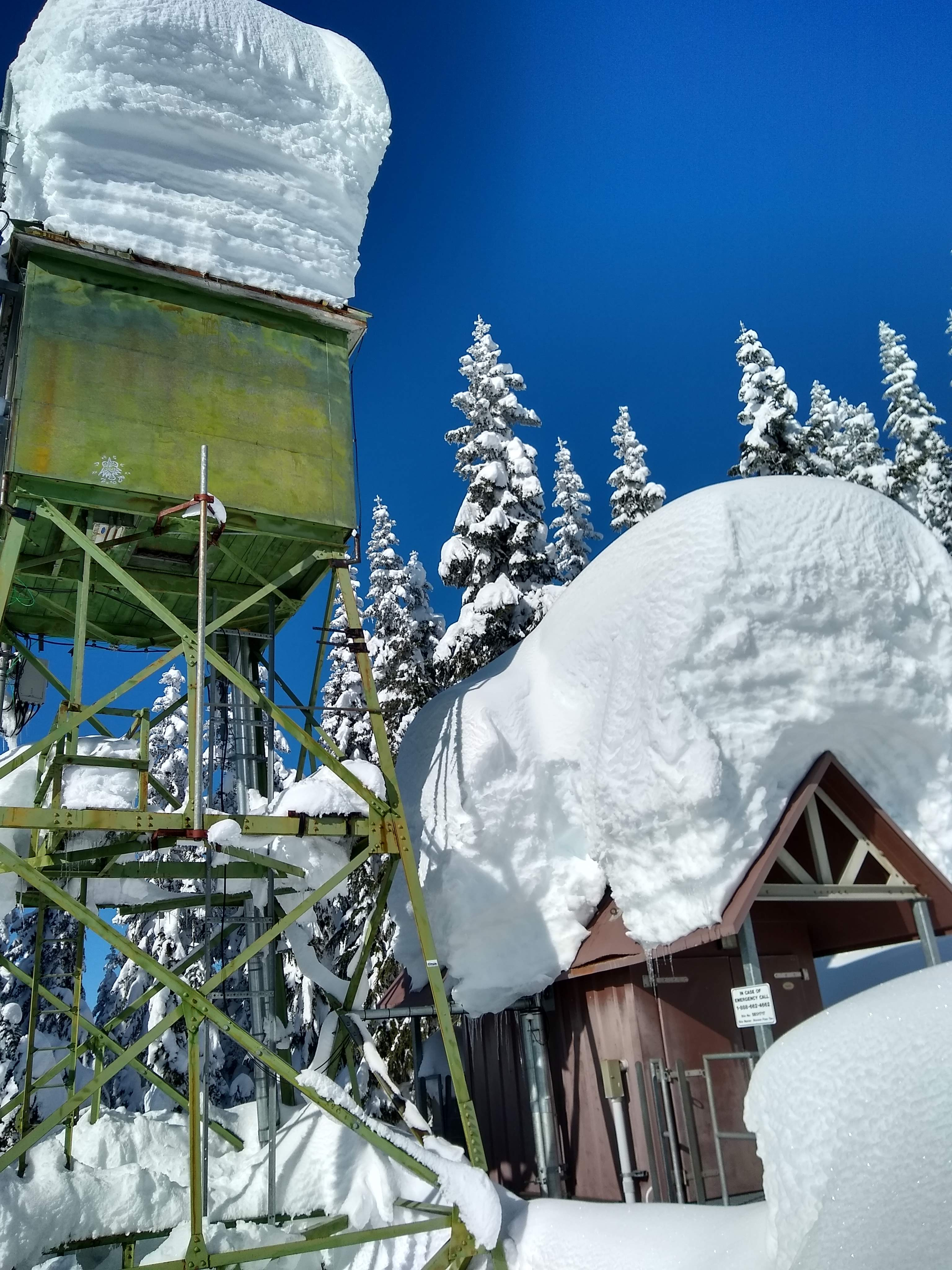 A communications tower covered in many feet of snow in the forest along the trail