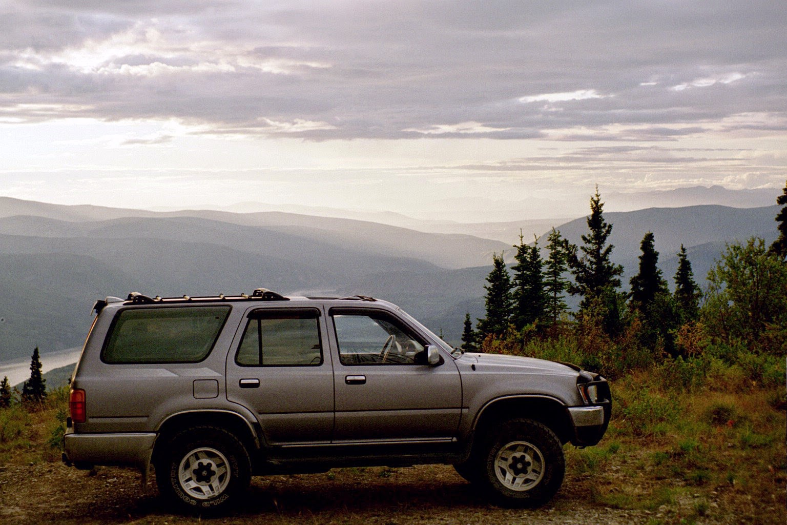 when you plan a road trip, make sure to get your car ready! An older gray SUV is parked on a high hill above a river.