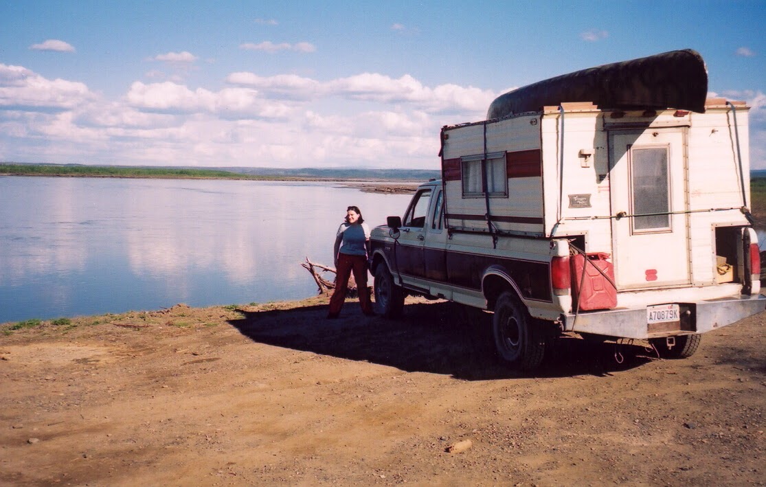 An old pick up truck with an even older camper shell on the back and a canoe on top. It is on a dirt road next to a wide river. A woman is standing next to the truck smiling.