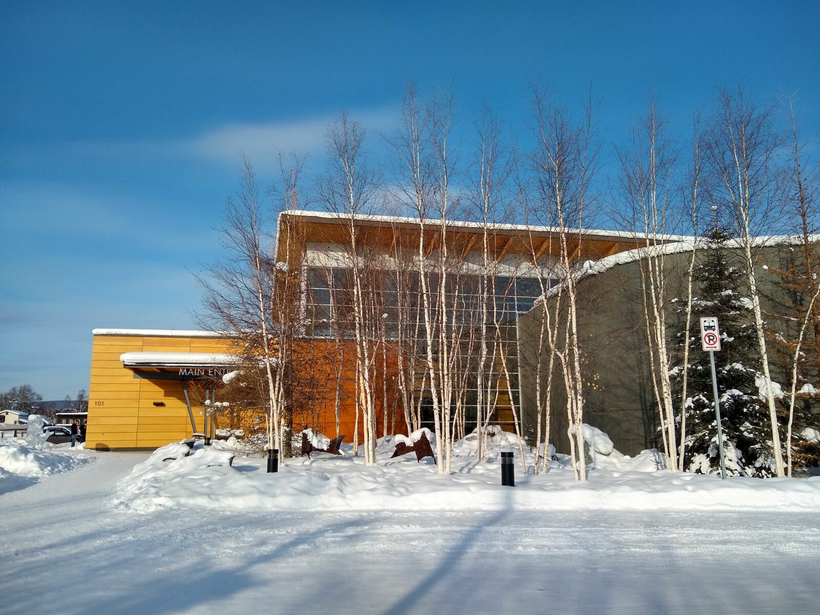 a modern wood and glass building surrounded by snow on a sunny day, the Morris Thompson Cultural Center is a great place to get information about things to do in Fairbanks as well as about the culture of Fairbanks