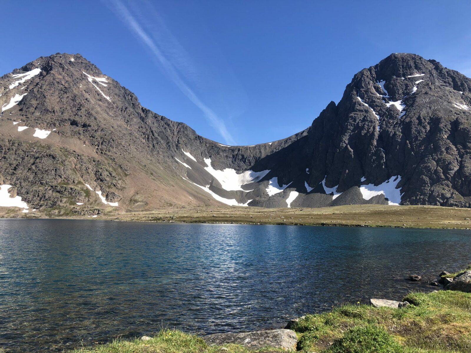 Rabbit Lake near Anchorage is an alpine lake surrounded by rocky mountains with bits of snow clinging all summer