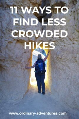 A hiker stands in a hole in a rock. She has one arm to the side and one above her head. There is bright sunlight on the other side of the hole. Text reads: 11 ways to find less crowded hikes