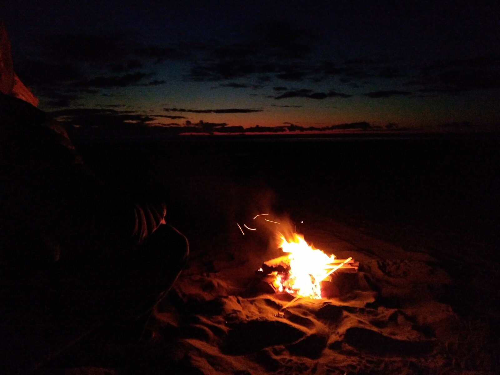 A fire in the sand on the beach after sunset. There is still a bit of sunset color on the horizon
