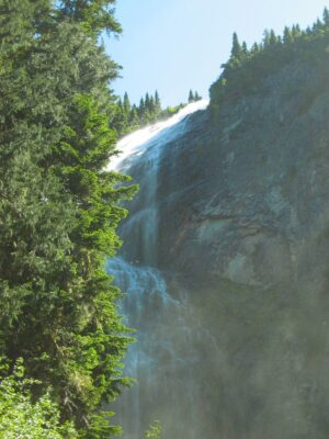 A wide, misty waterfall comes over a rock face with some evergreen trees around it