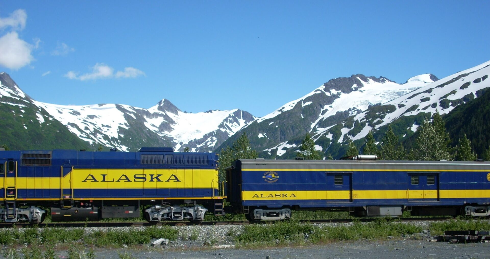 An engine and baggage car for the Alaska Railroad, an Alaska itinerary without a car. In the background are glacier covered mountains against a blue sky