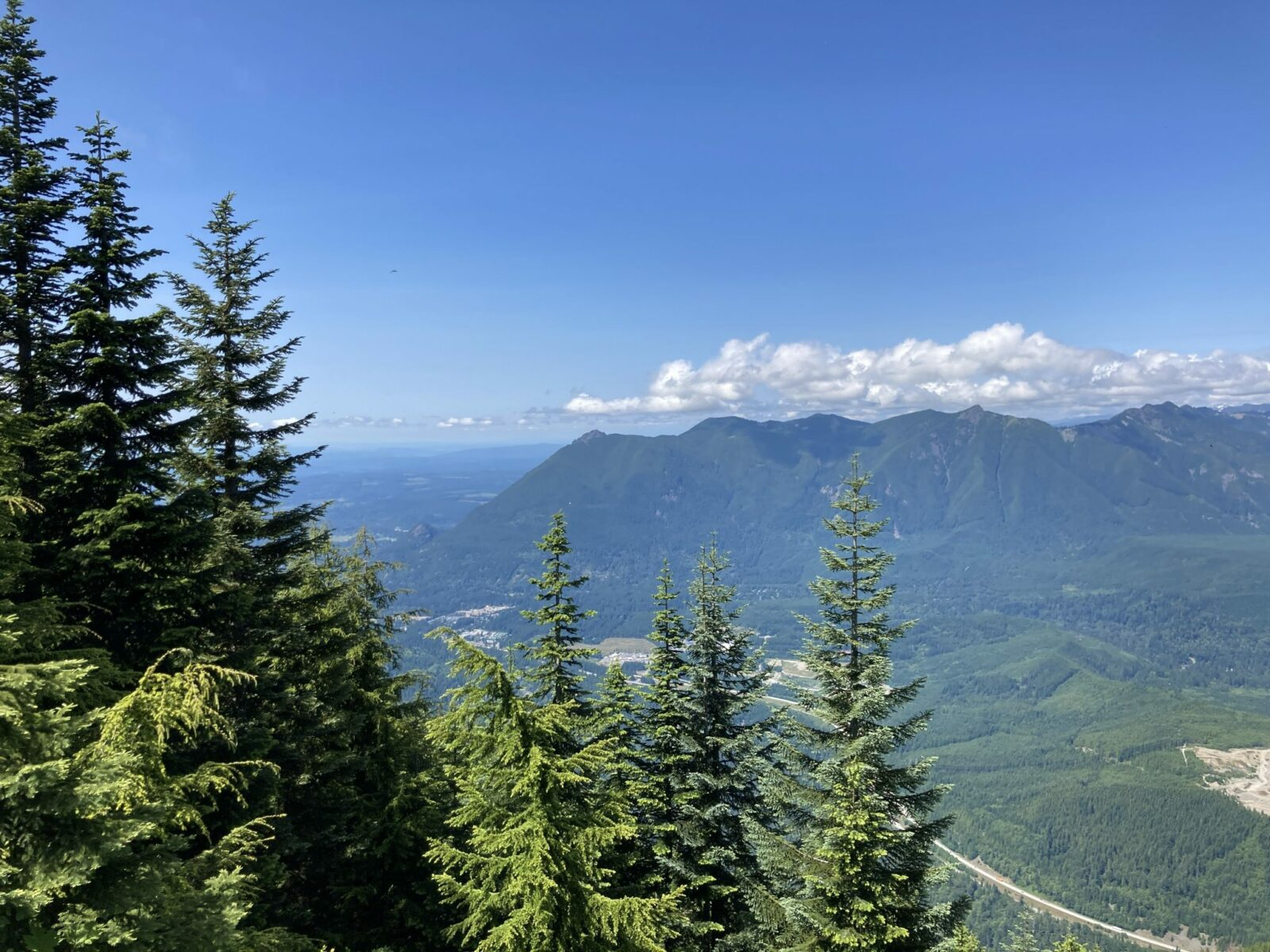 View from Mt Washington of the Snoqualmie Valley and North Bend and Mt Si in the distance. Mt Si is a forested high mountain with many others around it. Tere are evergreen trees in the foreground