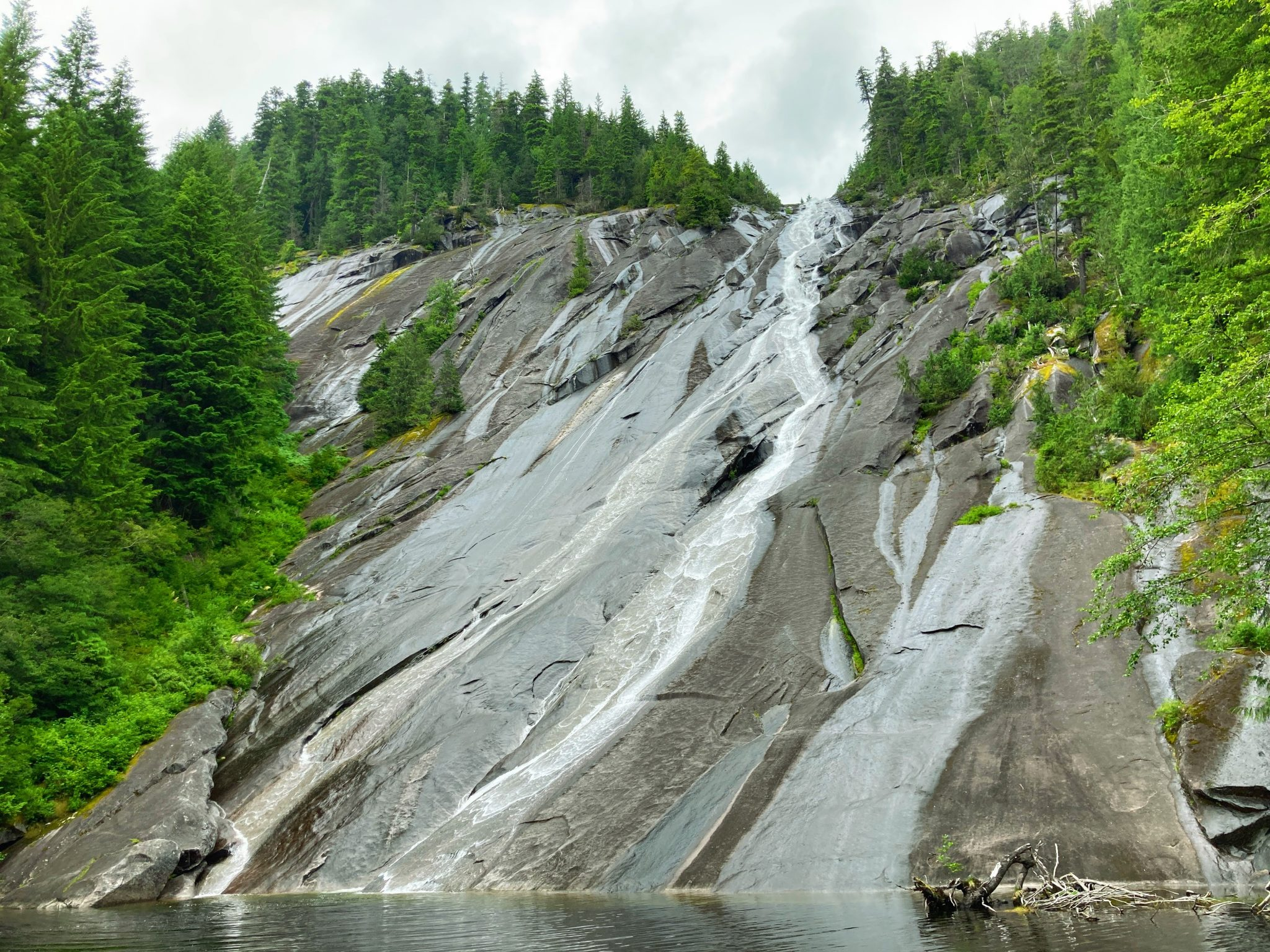 Otter Falls spills over a high rock and then spreads out over the flat surface of a rock next to a small lake. The giant rock face is surrounded by evergreen trees