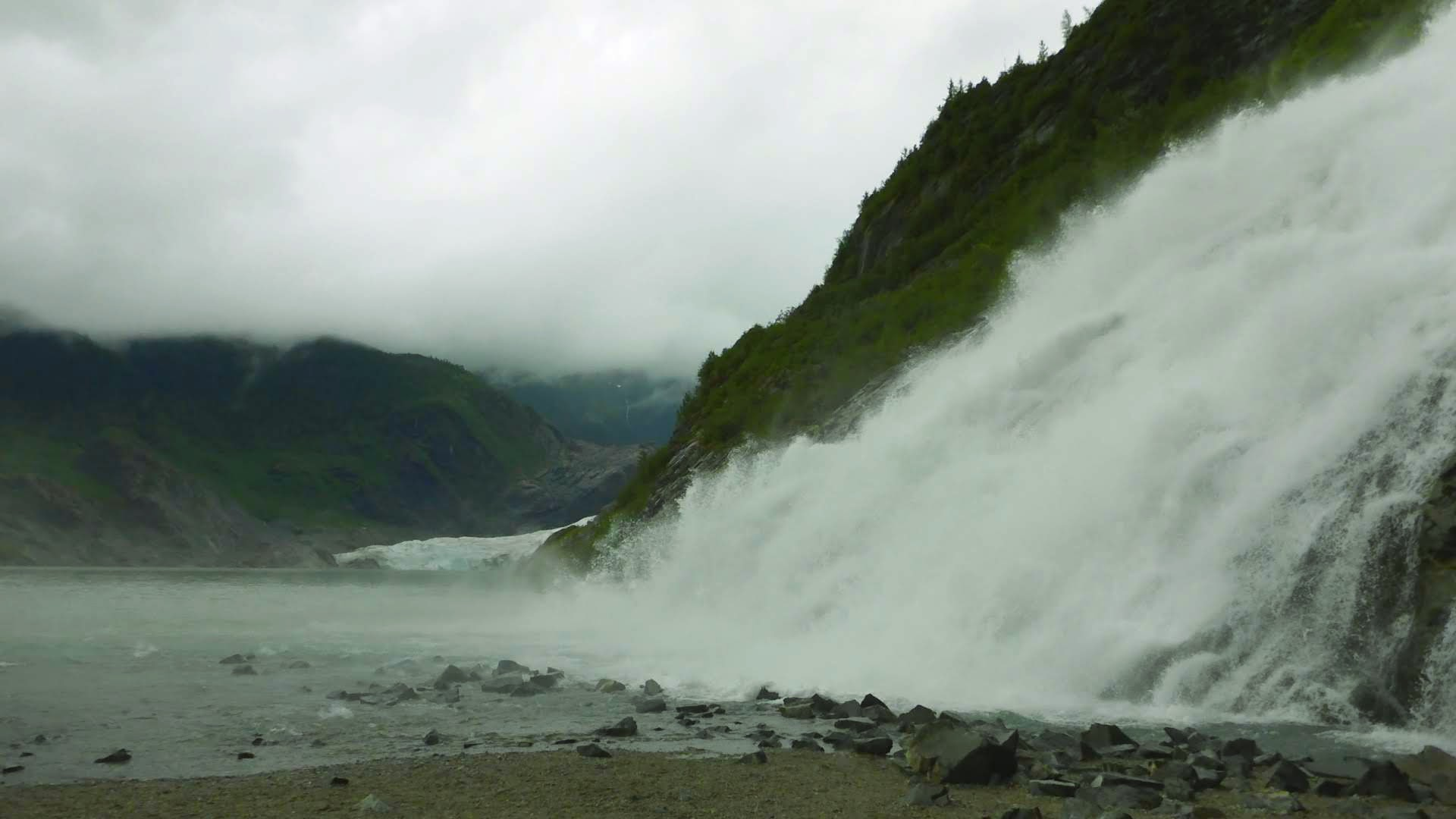 A waterfall tumbles from above against rocks into a glacier fed lake. There is a glacier in the background. It is a dark, overcast and rainy day on an Alaska itinerary