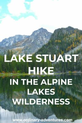 An alpine lake reflects the mountains around it. Text reads: Lake Stuart hike in the Alpine Lakes wilderness