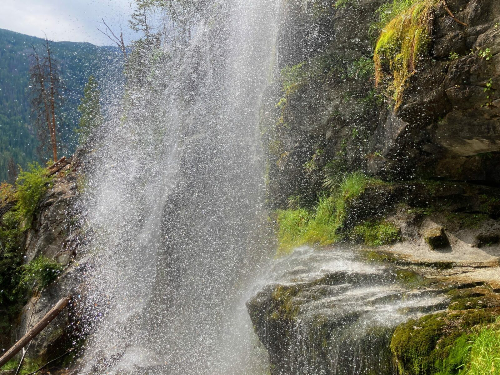 Spray from Silver Falls in the Entiat River Valleyl comes down a steep rock cliff. Some of the rocks are moss covered.