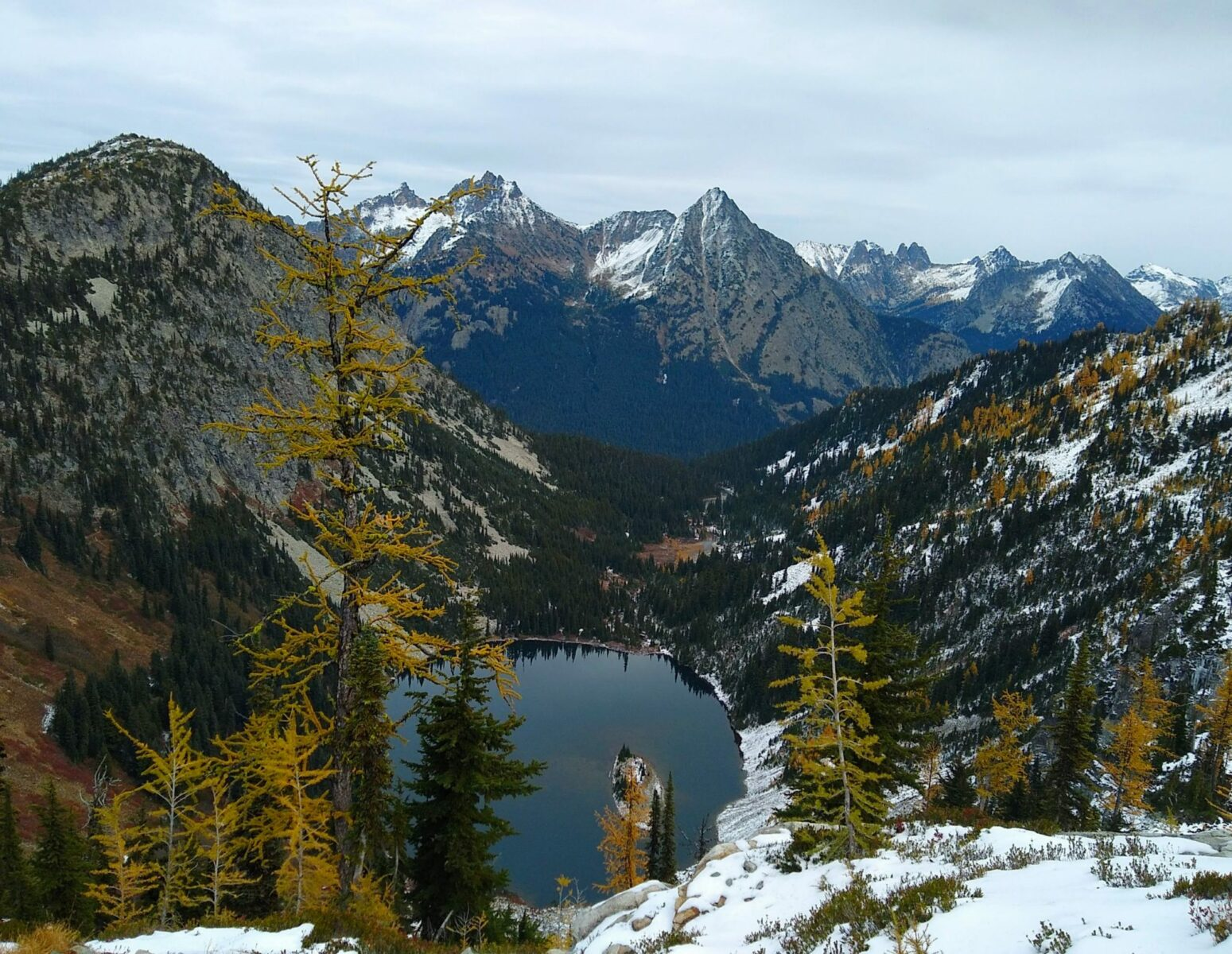 An alpine lake surrounded by forested mountains on the Maple Pass Loop in the North Cascades. There are golden larch trees in the foreground and high snowy mountains in the background