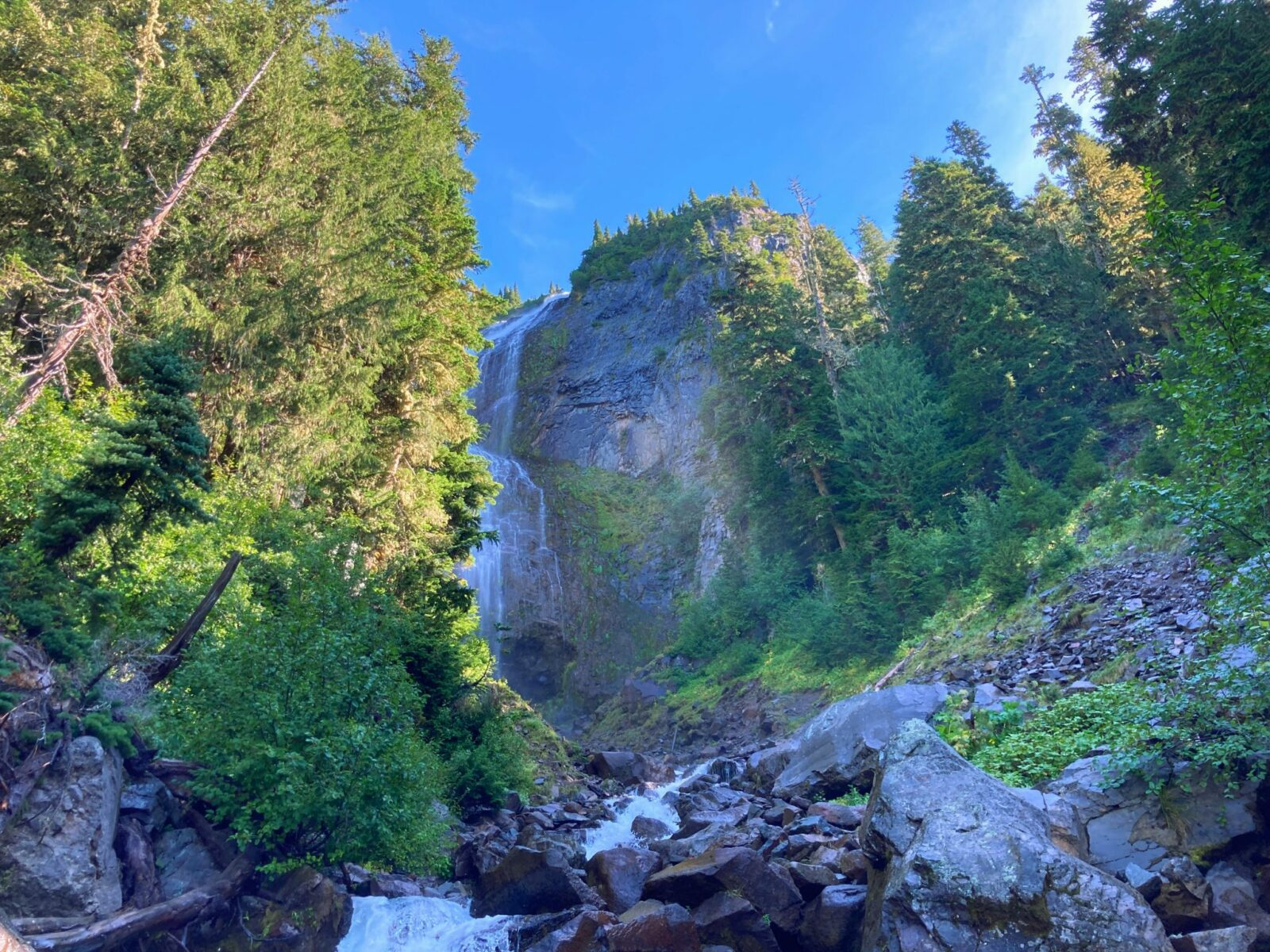 A steep and wide waterfall rolls over a cliff surrounded by forest. There are rocks and a creek in the foreground along the Spray Park trail in Mt Rainier National Park